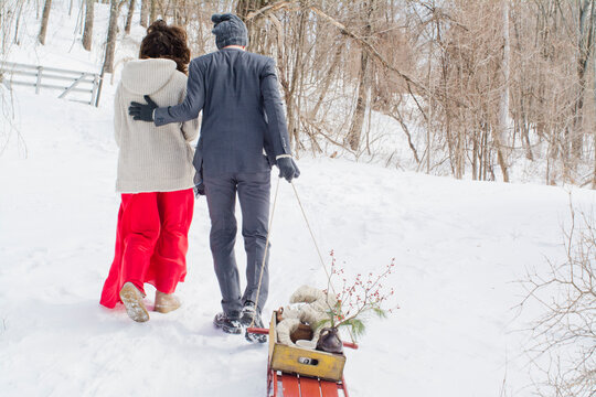 Mid adult couple walking through snowy field, man pulling sled, rear view