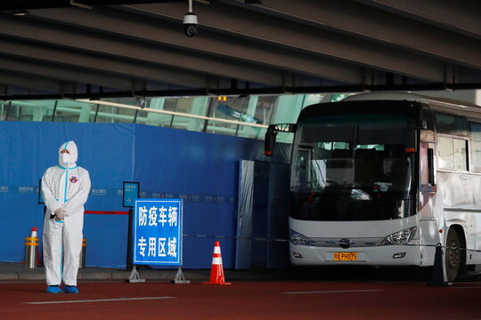 Staff member in protective suit stands next to a bus before the expected arrival of a World Health Organisation (WHO) team in Wuhan