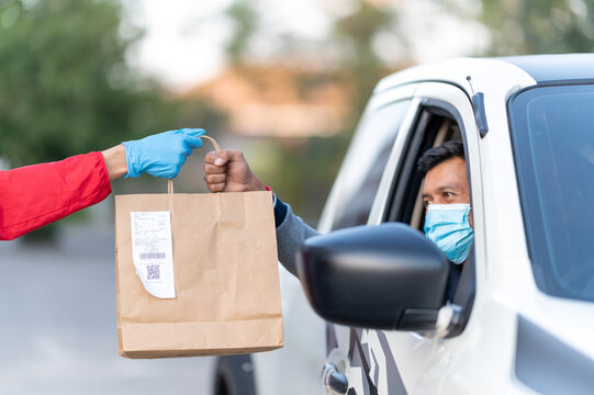 Small business and service concept with young man Wearing blue gloves Holding a paper bag to the customer with Drive in take away