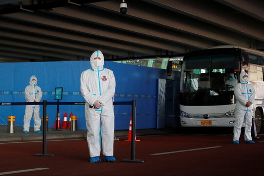 Staff members in protective suits stand guard next to a bus before the expected arrival of a World Health Organisation (WHO) team in Wuhan