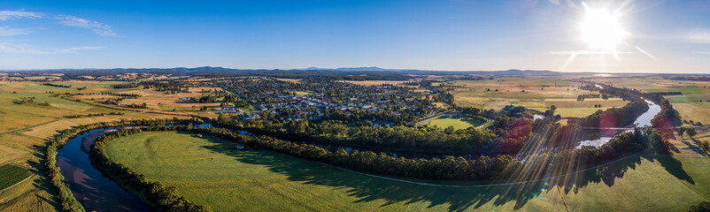 Fototapeta Amazing river bends among green fields and small town in Australian outback at sunset - wide aerial panorama