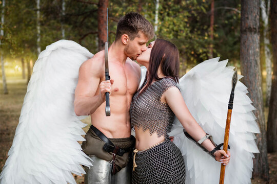 A loving couple of warrior angels kissing. Athletic man and woman in armor with weapons in their hands and white wings behind their backs against the backdrop of the park.