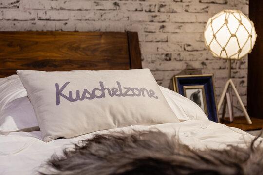 """Kissen mit der Aufschrft """"Kuschelzone"""" auf einem Bett"""