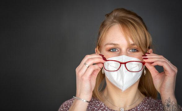 Problematisch: Mundnasenschutz und Brille - rotblonde Frau mit FFP2 Maske setzt ihre Brille auf - isoliert vor dunklem Hintergrund, Panoramaformat mit Textfreiraum