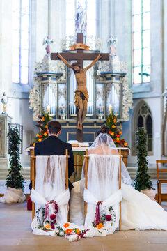 Hochzeitspaar sitzt während der Trauzeremonie vor dem Altar einer Kirche