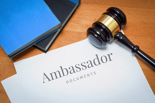 Ambassador. Document with label. Desk with books and judges gavel in a lawyer's office.
