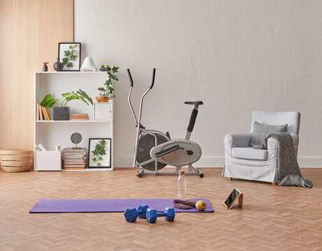 Training at home concept, interior, decorative sport in the room with gym fitness exercise purple mat, dumbbell and bicycle.