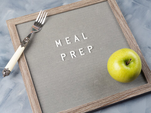 Meal prep concept with letter board, green apple and fork