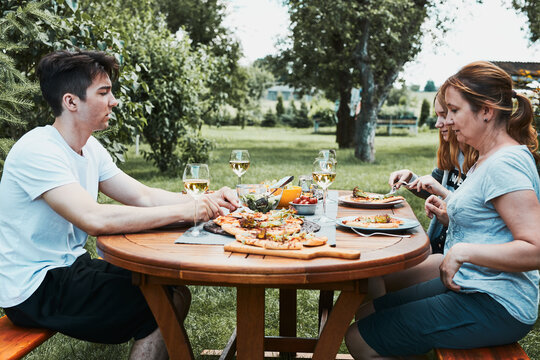 Family and friends having meal - pizza, salads, fruits and drinking white wine during summer picnic outdoor dinner in a home garden. Close up of people sitting at the table in a orchard in a backyard