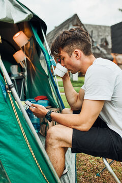 Young man drinking a coffee sitting at front of tent in the morning. Teenager enjoying free time during weekend trip in summer