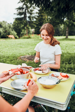 Family having breakfast outdoors on camping during summer vacation. Bread, cottage cheese, cold meat, tomatoes, fruits and coffee cups on table. Close up of outdoor table setting set on grass