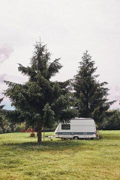 Caravan left among the pine trees on campsite