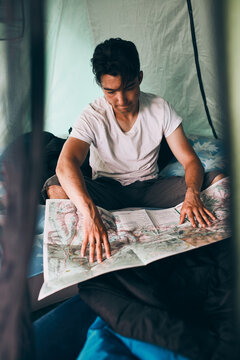 Young man looking at a map of mountain trails planning next trip on summer vacation sitting in a tent on camping. Concept of camp life