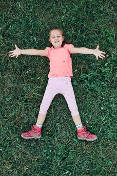 Little girl laying playing on grass enjoying summer day. Happy child playing in the field during weekend trip