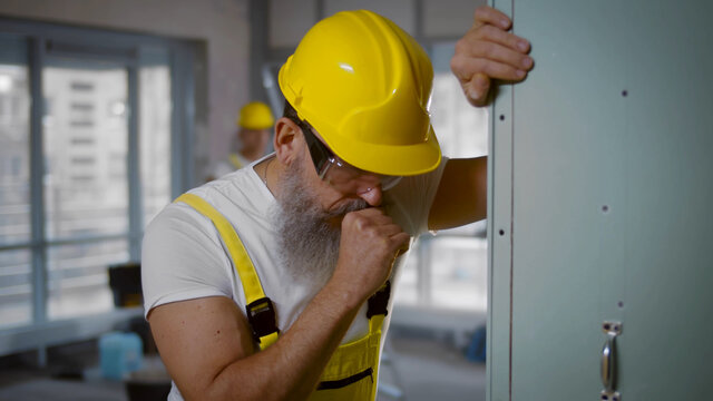 Senior construction worker sick and coughing in renovating apartment