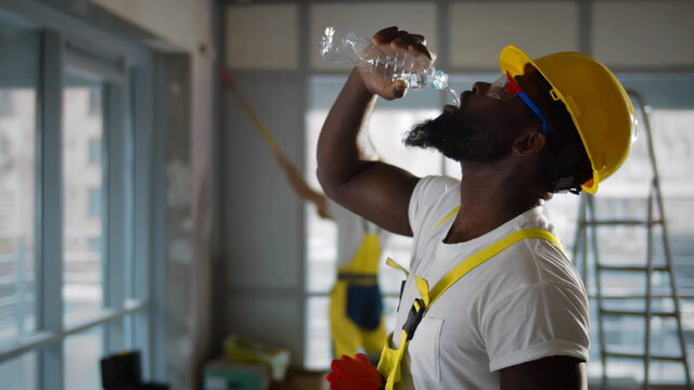 Tired african american construction worker drinking water