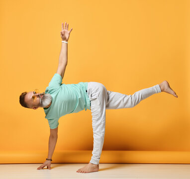 Mature handsome grey-haired brutal man wearing trendy sportswear practicing yoga in Ardha Chandrasana pose. Balance, harmony, strength and stretching. Studio shot on yellow background. Side view