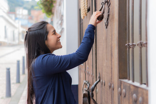 Young happy Hispanic female in a blue jacket knocking on the door
