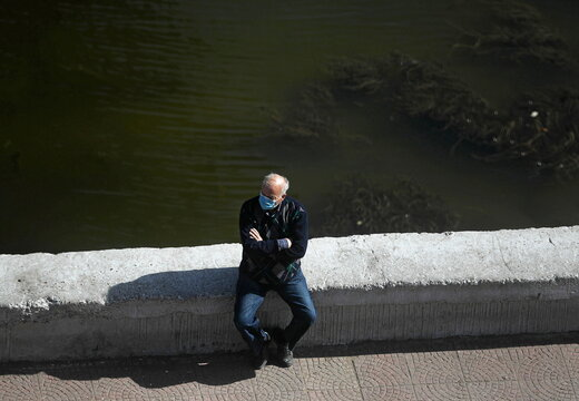 A man wearing a protective mask sits along the bank of the Nile river amid the coronavirus disease (COVID-19) outbreak in Cairo