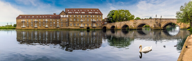 The mill and old bridge at Riverside, Godmanchester reflected in the calm waters of the River Great Ouse as a swan serenely glides past in springtime
