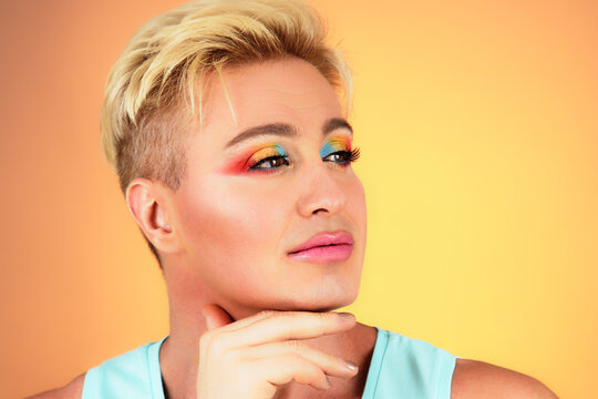 Beauty Fashion guy with Colorful Art Makeup, Blonde Hair. Sexy man with Bright make up portrait. Handsome gay smiling, healthy male skin, lgbtq concept. Fashionable trendy style