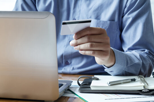 Midsection Of Man Holding Credit Card While Using Laptop For Online Shopping On Table