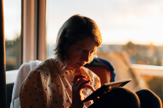 a woman sitting indoors nearby a big window at sunset using a tablet. Wireless technology concept