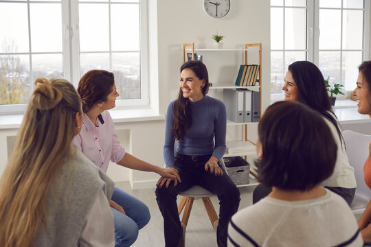 Happy thankful young women sitting in circle, smiling, talking and sharing positivity in group meeting or therapy session with coach. Female community, support and overcoming problems together concept