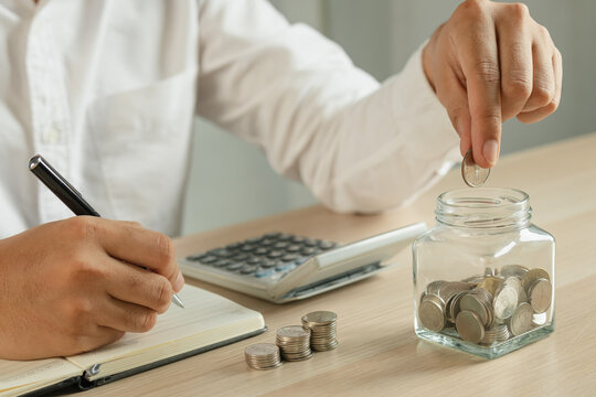 Close up hand of young asian businessman puts a coin into the jar to calculate and financial plans to spend enough money on his income for saving money.