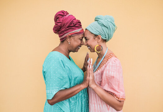 Happy african mother and adult daughter together while wearing traditional dress and turban