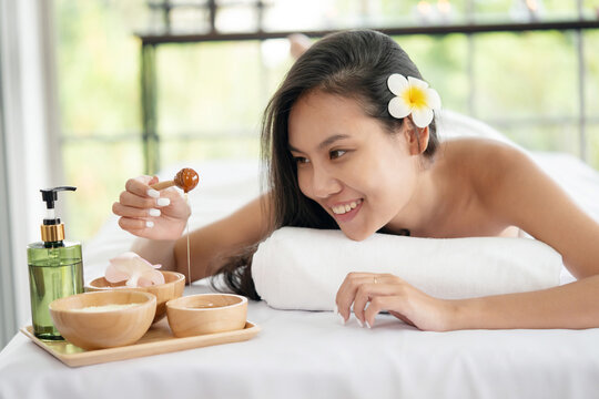 Woman Lying Down on Massage Bed Holding Honey Stick Waiting For Body Care Treatmen