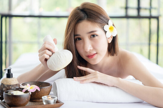 Asian Woman Lying Down on Massage Bed Holding Herbal Compress Ball  Waiting For Body Care Treatment