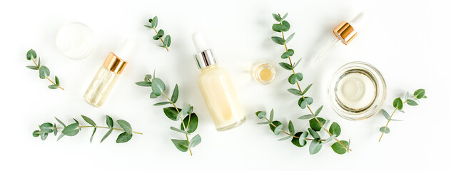 Eucalyptus essential oil, eucalyptus leaves on white background. Natural, Organic cosmetics products. Medicinal plant. Natural Serums. Flat lay, top view.