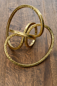 Gold metal torus infinity shape on dark hickory wood
