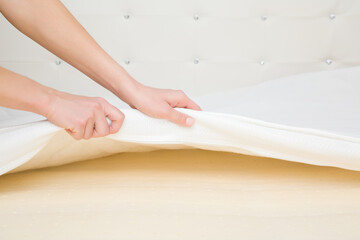 Young adult woman hands opening white cover and showing yellow rubber foam inside orthopedic mattress. Closeup. Wall mural