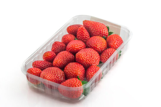 Fresh organic strawberries in plastic box on a white background