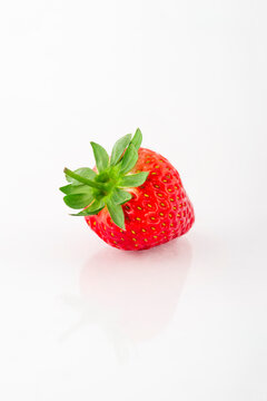 Fresh organic strawberries on a white reflective surface. Close up shot.