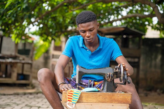image of african young guy, with sewing machine- local made face mask production concept