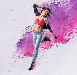 Fit dancer jumping into the paint splash