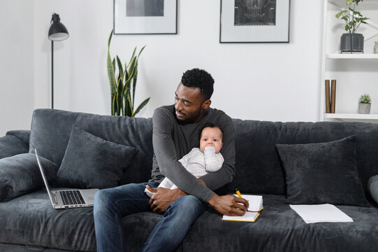 A busy freelancer, student dad with an infant sit on the couch, he works from home. A young African-American father using laptop for remote work and looking after his cute baby daughter