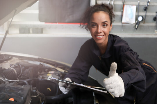 Female auto mechanic giving thumb up at garage, car service technician checking and repairing the customer's car at automobile service center, vehicle repair service shop concept