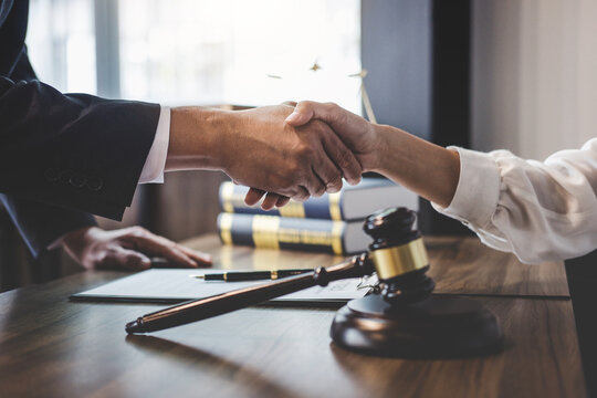 Close-up Of Lawyer And Customer Shaking Hands On Table