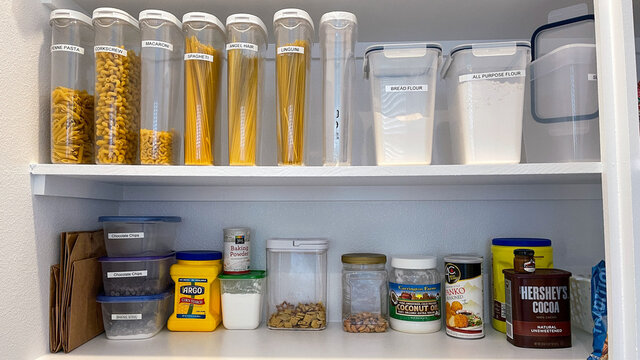 A home pantry that is organized with various products in put away in a tidy manner.