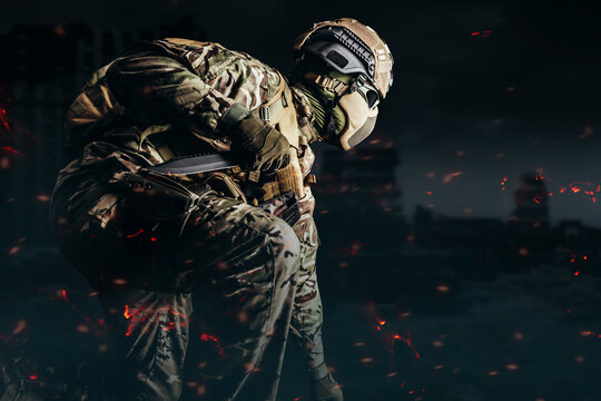 Photo of a fully equipped soldier in armored vest, helmet, face glasses and protection kneeling and attacking with knife on shaded destructed city background.