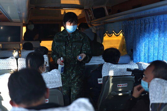 A female soldier checks the temperature of the media onboard a bus in Tainan,