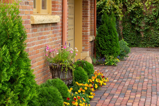 Full frame texture background of a 19th century red clay brick wall with charming weathering from age, with view of a window and attractive foundation plants