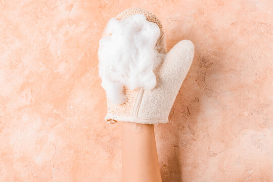 Female hand with massage glove on color background