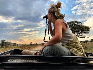 Fototapeta Woman Holding Binoculars While Sitting On Jeep Against Cloudy Sky obraz