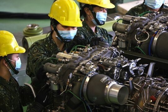 Air Force officers demonstrate maintenance work on an AH-64 Apache attack helicopter at a military base in Tainan
