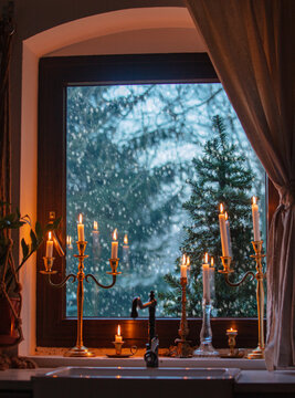 candles on the window in kitchen during a snowfall, trees on the background